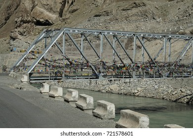 Buddhist prayer flags protect a bridge over the Inuds River in Ladakh, India