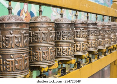 Buddhist prayer wheels with ancient art wall, Nepal