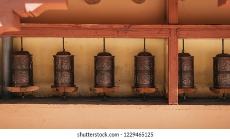 Buddhist prayer wheels in Tibetan monastery with written mantra. Ladakh, India