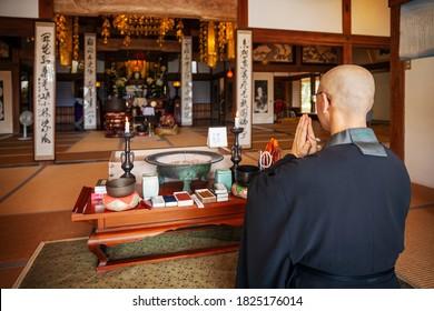 Buddhist priest kneeling in Buddhist temple, praying.