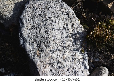 Buddhist religious spiritual text symbols inscriptions in old Stones near Manang, Annapurna Conservation Area, Himalaya,  Nepal