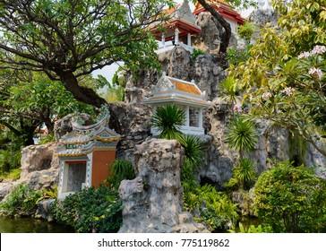 Buddhist spirit house shrine stand on stones near temple in Thailand