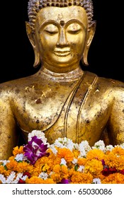 a buddhist statue with garland isolated on black background, Thailand