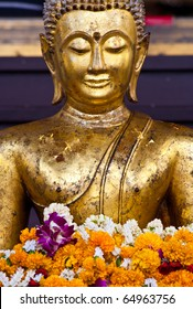 a buddhist statue with garland, Thailand