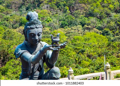 Buddhist statues praising and making offerings to the Tian Tan Buddha. The Po Lin Monastery and the Lantau Peak in the background, in Hong Kong.