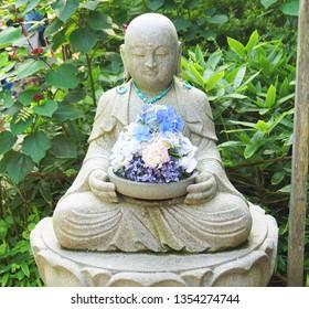 Buddhist stone sculture decorated with blue hydrangea flowers at Fugenzan Meigetsu-in (also known as  Ajisaidera or Ajisai Temple), Kamakura, Kanagawa, Japan