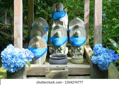 Buddhist stone scultures decorated with blue hydrangea flowers at Fugenzan Meigetsu-in (also known as  Ajisaidera or Ajisai Temple), Kamakura, Kanagawa, Japan