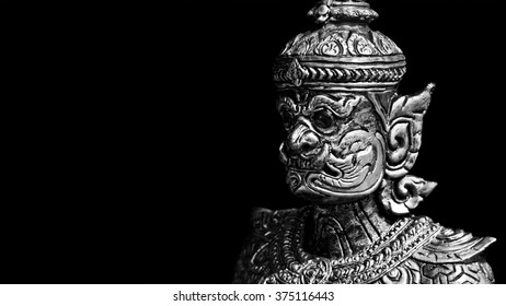 Buddhist stone statue. Giant guardian on black background