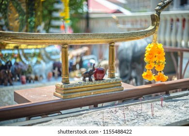 A buddhist temple with an offering of a single apple next to a miniature elephant statue.