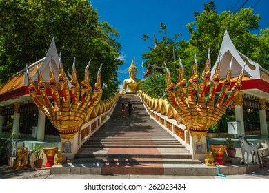 Buddhist temple with stairs and statues against a blue sky