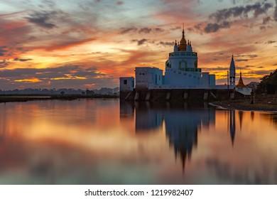 Buddhist temple at sunset reflecting in lake near U bein bridge at Amarapura ,Mandalay, Myanmar.