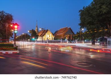 Buddhist temple of Wat Pra Tard Chang Kum in Nan, Thailand with trafic jam at night scene.