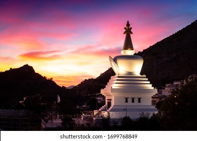 a Buddhist white monument with a golden peak at sunset. Benalmadena Pueblo, Benalmadena, Costa del Sol, Malaga Province, Andalusia, Spain, Western Europe.