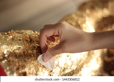 Buddhist woman hands are closing gold leaf on the Buddha image. At Phra Pathom Chedi Nakhon Pathom Province on 21 June 2019
