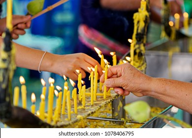 Buddhists make merit, Placing a lighted candle with candles frame on the altar of Buddha at temple. Selective focus.
