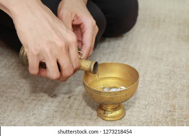 Buddhists make merit,Pouring water from the bottle into the cup, after a good deed and share the wealth to Buddhism. Means to share good to others. Selective focus.