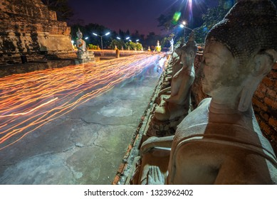 Buddhists people walking (motion blur)  with lighted candles in hand around a ancient temple on Magha Puja day at Ayutthaya province of Thailand.