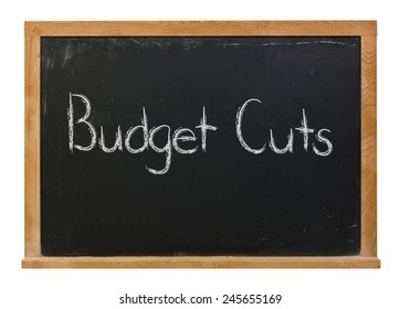 Budget cuts written in white chalk on a black wood framed chalkboard isolated on white