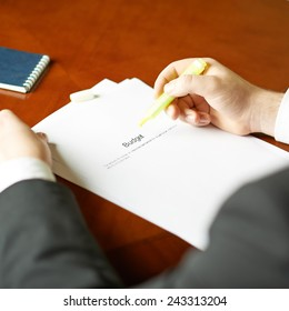Budget definition as a shallow depth of field close-up composition of a man in a business suit working with the text
