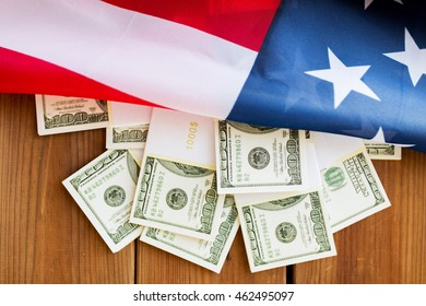 budget, finance and nationalism concept - close up of american flag and dollar cash money packets