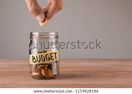 Budget. Glass jar with coins and an inscription budget. Man holds  coin in his hand