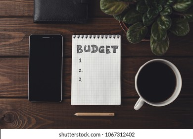 Budget planing concept. Top view of notepad with word Budget, mobile phone, cup of coffee wooden background. Write idea success solution, toned