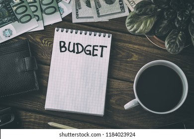 Budget planing concept. Top view of notepad with word Budget and cup of coffee on wooden table background. Write idea success solution concept, vintage toned