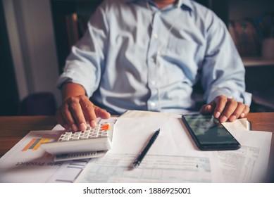 Budgetplanungs-Konzept, Tragemaske des Buchhalters berechnet die Jahressteuer des Unternehmens. Kalender 2021 und Formulare zur Einkommensteuer für Personen, die Einkommen nach US-Recht auf dem Schreibtisch des Hauses haben.