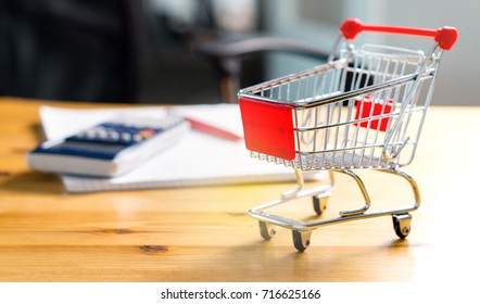 Budget of poor and low income family. Rising food and grocery store prices and expensive daily consumer goods concept. Miniature shopping cart and trolley on table with calculator, pen and paper.