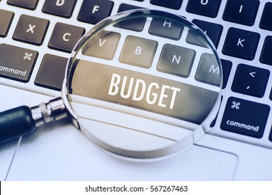 BUDGET word written on keyboard view with magnifier glass. Business finance marketing content concept