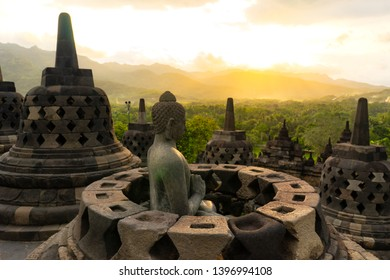 Budha statue in Borobudur temple - Yogyakarta / Indonesia shot at sunrise / sunset with glowing gold sun rays and hills full of green trees as background.