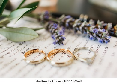 Budva, Montenegro - 08 september 2020: Close-up of wedding rings of the bride and groom and white gold rings with inscriptions on a piece of paper with an oath and a sprig of lavender.