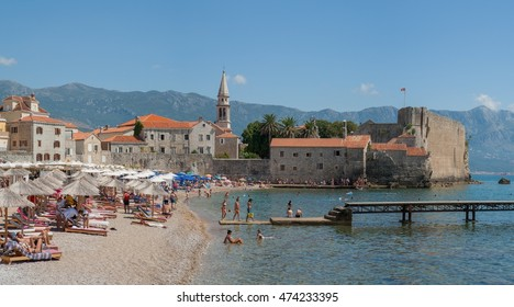 Budva, Montenegro - August 19, 2016: City beach Richardova Glava near Old Town and fortress in Budva, Montenegro. In sight: beach Richardova Glava, Sveti Ivan bell tower and walls of the citadel,