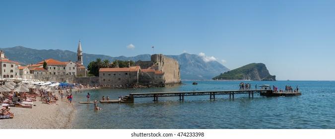 Budva, Montenegro - August 19, 2016: City beach Richardova Glava near Old Town and fortress in Budva. In sight: beach Richardova Glava, Sveti Ivan bell tower and citadel, Sveti Nikola island.