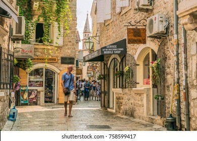 Budva, Montenegro - August 20, 2017: Fragment of the old town of Budva, Montenegro. The first mention of this city - more than 26 centuries ago. We see old houses, a very narrow street, cafes, shops.