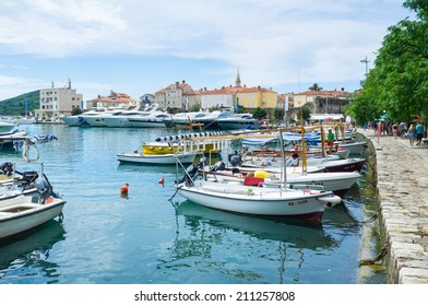 BUDVA, MONTENEGRO - JULY 12, 2014: Slovenska Obala is the city promenade, leading to the citadel in the old town with many tourist boats and luxury yachts in the small shipyard, on July 12 in Budva