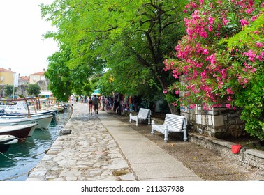 BUDVA, MONTENEGRO - JULY 12, 2014: The Slovenska Obala is the city promenade with the cozy benches, shady trees, beautiful flower bushes and numerous souvenir shops and cafes, on July 12 in Budva