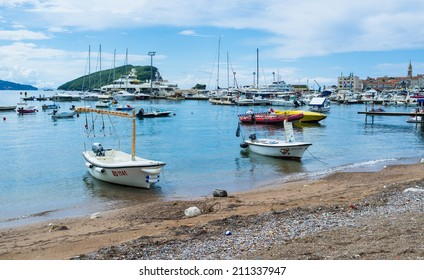 BUDVA, MONTENEGRO - JULY 12, 2014: The small tourist boats moored next to the old town with the Sveti Nikola Island on the background, on July 12 in Budva