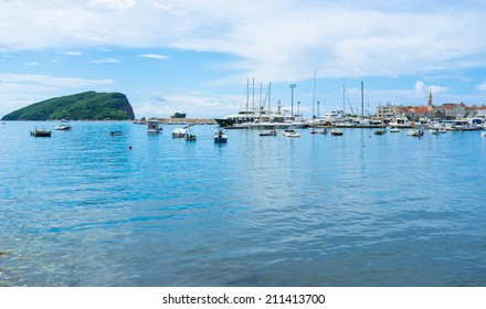 BUDVA, MONTENEGRO - JULY 12, 2014: The Sveti Nikola Island and the old citadel, surrounded by the fishing and tourist boats, luxury yachts, on July 12 in Budva