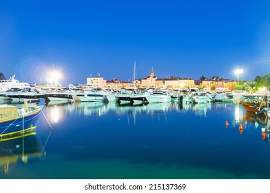 BUDVA, MONTENEGRO - JULY 12, 2014: The small port with the medieval town-fortress on the background in bright illumination, on July 12 in Budva.