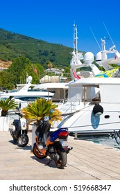 BUDVA, MONTENEGRO - JULY 12, 2015: Motobike in th? sea port with many tourist boats and luxury yachts in the small shipyard