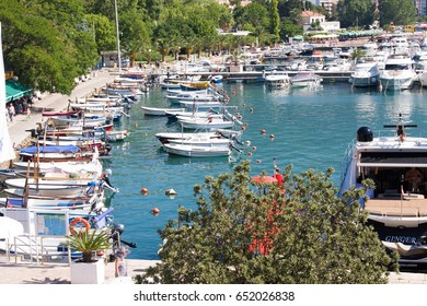 BUDVA, MONTENEGRO - JULY 12, 2015: Slovenska Obala is city promenade, leading to citadel in old town with many tourist boats and luxury yachts in the small shipyard