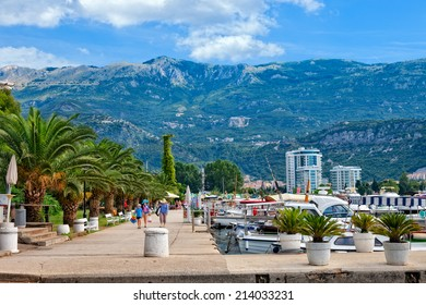 BUDVA, MONTENEGRO - JULY 18: Unknown people walking on the promenade of Slovenska Obala with boats and palm trees in port, on July 18, 2014 in Budva, Montenegro.