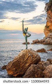 BUDVA, MONTENEGRO - October 01, 2017: Beautiful and elegant sculpture of a gymnast, located on a rocky rock near the beach Morgen and the old town of Budva in Montenegro.