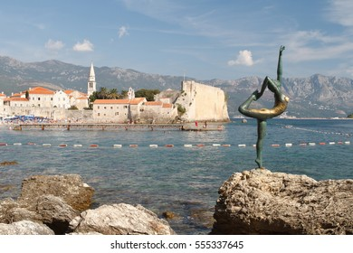 BUDVA, MONTENEGRO - September 13, 2016: Statue of Ballet Dancer in Arabesque Position. Mogren Beach. Background Blurred Old Town Budva, Montenegro.