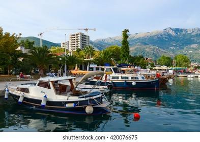 BUDVA, MONTENEGRO - SEPTEMBER 15, 2015: Unidentified people are relaxing on the promenade of the popular resort of Budva near the berth of pleasure boats, Montenegro