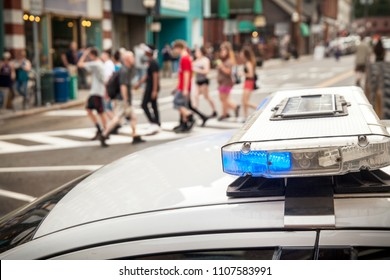 A bue light flashes on the top of a police cruiser as pedestrians cross the street in the background.