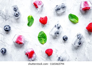 Bueberrie and raspberrie in ice cubes on stone top view
