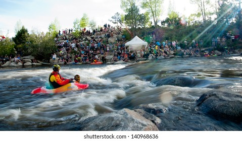 Buena Vista, CO/USA - MAY 25, 2013: EJ Jackson (foreground) watches his son Dane prepare break the World Record in kayak freestyle points.  Shot at South Main  playhole on Arkansas River in Buena Vista, CO.