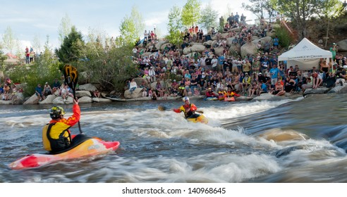 Buena Vista, CO/USA - MAY 25, 2013: EJ Jackson (foreground) watches his son Dane Jackson break the World Record in kayak freestyle points.  Shot at South Main playhole on Arkansas River in Buena Vista, CO.